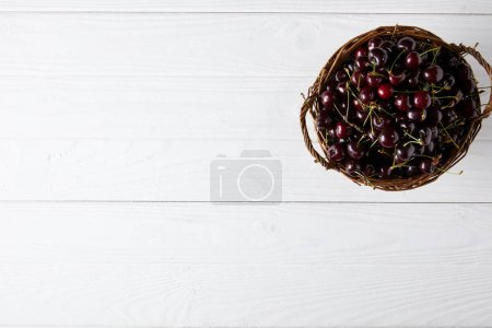 top view of ripe cherries in rustic basket on white wooden surface