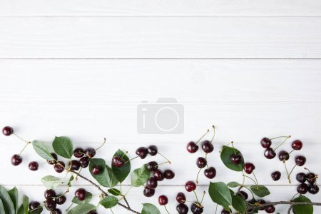 top view of red and rainier cherries spilled on white wooden surface with leaves