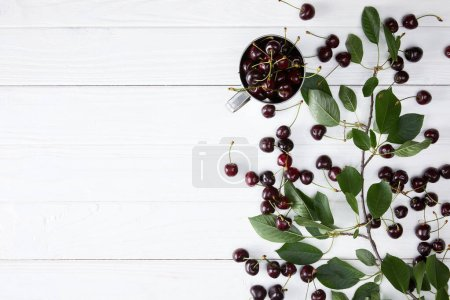 Photo for Top view of ripe cherries in cup and spilled on white wooden surface with leaves - Royalty Free Image