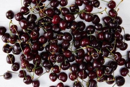 top view of fresh ripe sweet cherries spilled on white wooden surface