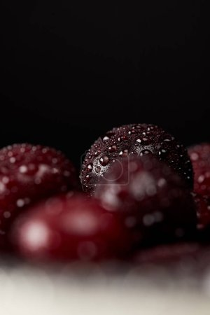 close-up shot of fresh red cherries covered with water droplets isolated on black