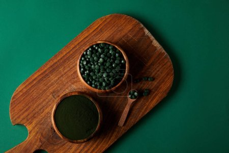 top view of cutting board, wooden spoon,  bowls with spirulina powder and spirulina in pills on green table