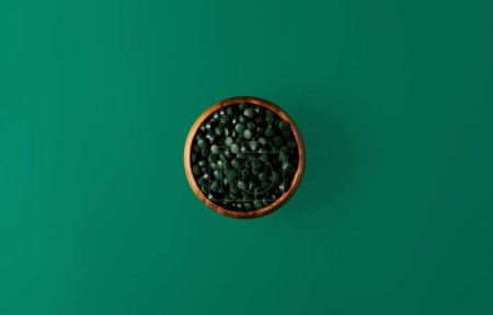 top view of wooden bowl with pile of spirulina pills isolated on green