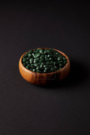 wooden bowl with pile of spirulina pills on grey table