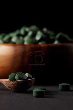 selective focus of wooden spoon and bowl with pile of spirulina pills on black background