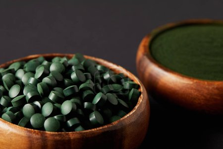 close up view of wooden bowls with ground spirulina and spirulina in pills on grey background