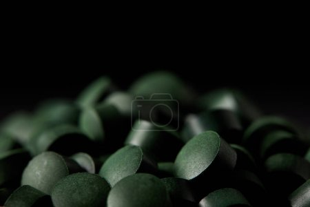 selective focus of pile of spirulina pills isolated on black background