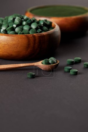 selective focus of wooden spoon, bowls with ground spirulina and spirulina in pills on grey table
