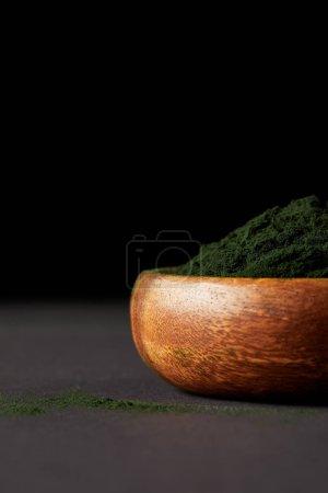 selective focus of spirulina algae powder in wooden bowl on black background