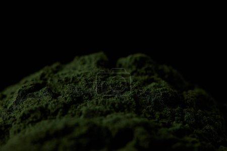 selective focus of spirulina algae powder isolated on black background
