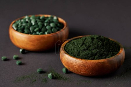selective focus of wooden bowls with ground spirulina and spirulina in pills on grey table