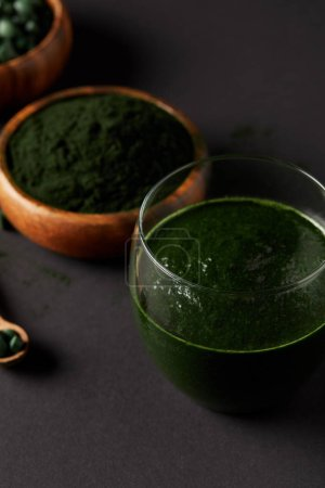 selective focus of wooden spoon, glass of fresh smoothie from spirulina, bowls with spirulina powder and spirulina pills on grey table
