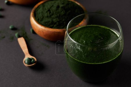 close up view of wooden spoon, glass of smoothie from spirulina, bowls with spirulina powder and spirulina pills on grey table
