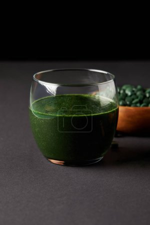 glass of fresh smoothie from spirulina and wooden bowl with spirulina pills on black background