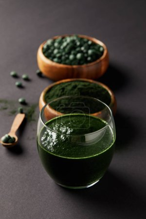 selective focus of arranged wooden spoon, glass of spirulina smoothie, bowls with spirulina powder and spirulina pills on grey table