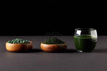 glass of spirulina smoothie, bowls with spirulina powder and spirulina pills on black background