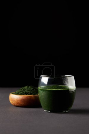 Photo pour Spiruline fraîche boisson dans le verre et la Spiruline en poudre dans un bol en bois sur fond noir - image libre de droit