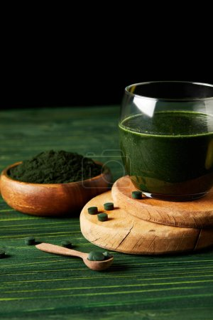 wooden slices with fresh spirulina drink in glass, wooden spoon and spirulina powder in wooden bowl on black background on green wooden table