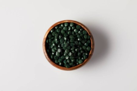 top view of wooden bowl with pile of spirulina pills on grey table