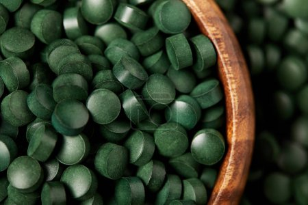 close up view of wooden bowl with pile of spirulina pills