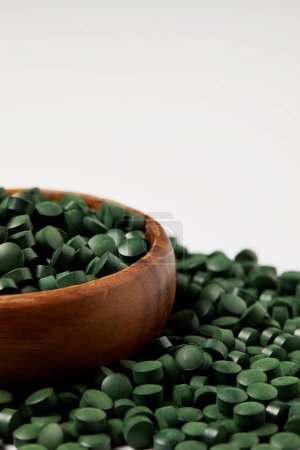 close up view of wooden bowl and pile of spirulina pills isolated on grey background