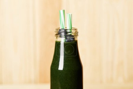 bottle of spirulina smoothie with blueberries and drinking straw on blurred background