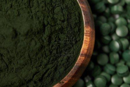 selective focus of spirulina pills and spirulina powder in bowl