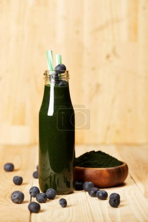 bowl with spiruluna powder, bottle of spirulina smoothie with blueberries and drinking straw on wooden table