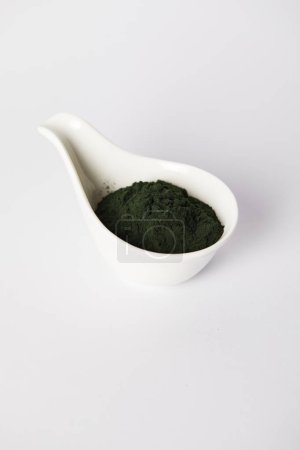 spirulina algae powder in bowl on grey background