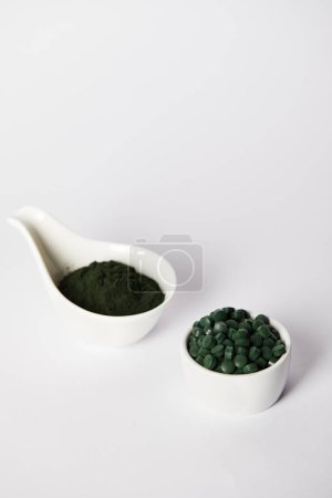 spirulina powder and spirulina pills in bowls on grey background