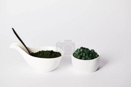 spoon, spirulina powder and spirulina pills in bowls on grey background