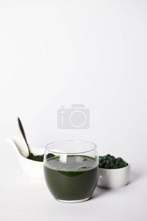 fresh spirulina drink in glass, spoon, spirulina powder and spirulina pills in bowls on grey background