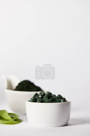 selective focus of leaves, bowls with spirulina pills and spirulina powder on grey background