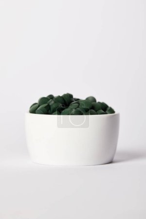 pile of spirulina pills in bowl on grey background