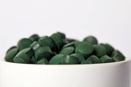 selective focus of pile of spirulina pills in bowl isolated on grey background
