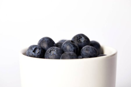 selective focus of blueberries in bowl isolated on white background