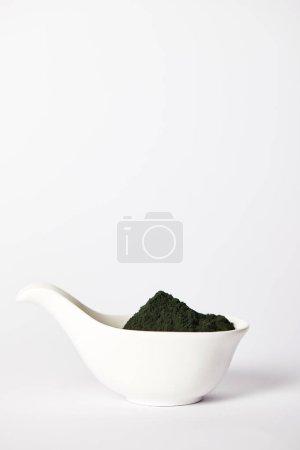 spirulina algae powder in bowl isolated on grey background