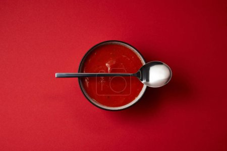 top view of delicious red tomato soup in plate and spoon on red table