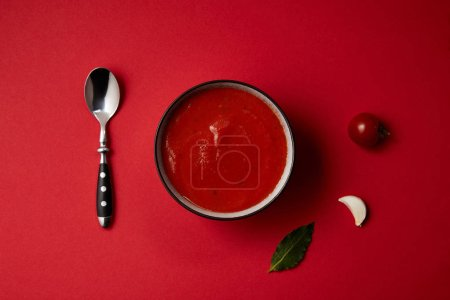 top view of tasty tomato soup in plate, spoon, fresh tomato and garlic on red table