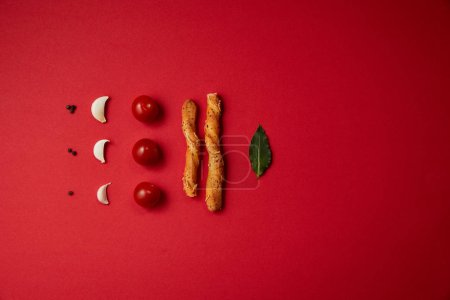 food styling of tasty tomatoes, garlic, bread sticks and bay leaf on red table
