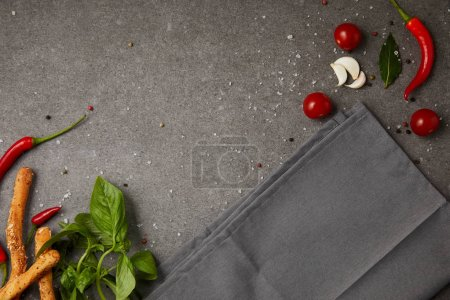 top view of grey napkin with vegetables and bread sticks on grey table