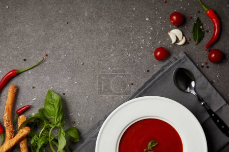 Photo for Top view of tasty tomato soup in plate on napkin on grey table - Royalty Free Image