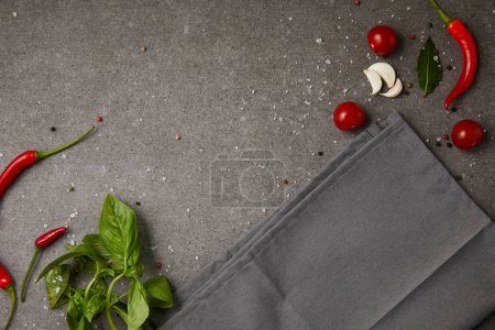 top view of grey napkin with vegetables on grey table