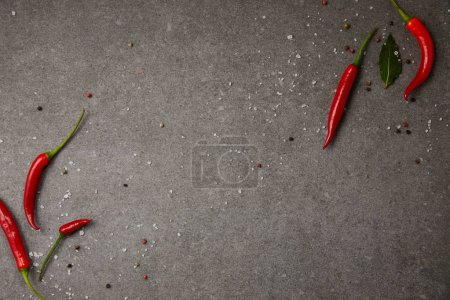 top view of chili peppers and scattered spices on grey table