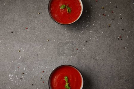 elevated view of two plates with tasty tomato soup on grey table