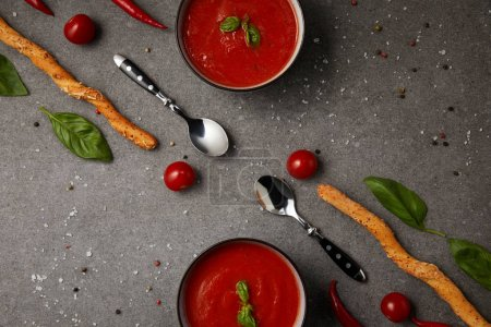 food styling of tasty tomato soup and bread sticks on grey table