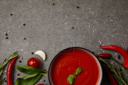 Photo for Top view of delicious tomato soup and vegetables on grey table - Royalty Free Image