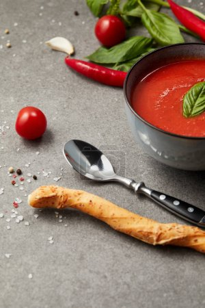 bread stick and spoon near plate with tomato soup on grey table