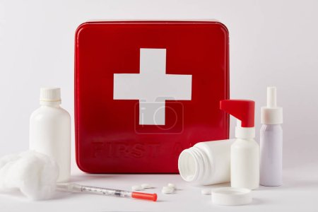 first aid kit box with blank medical bottles, syringe and cotton swab on white