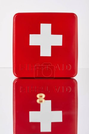 red first aid kit box with omega capsule on reflective surface